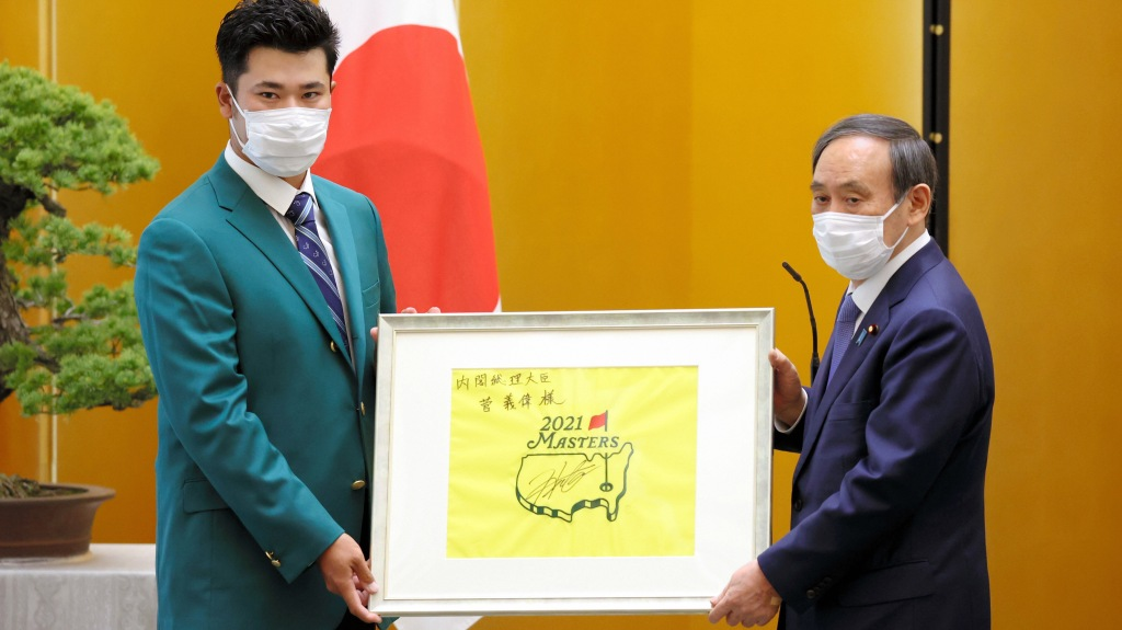 Hideki Matsuyama wearing the green jacket poses with prime minister Yoshihide Suga during the prime minister's award ceremony